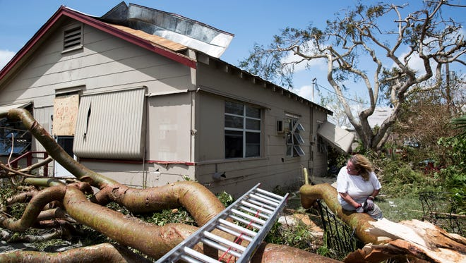 Margie Hackett looks back at her home and the near collision a downed tree almost incurred the morning after Hurricane Irma hit Goodland, Fla. on Monday, September 11, 2017.