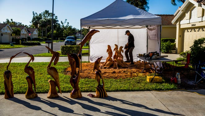 Hector Najera Sola, owner of Naples Mahogany Chainsaw Art, works on a dolphin sculpture outside of Kathleen Radcliffe's Bonita Springs home on Thursday, Nov. 30, 2017.