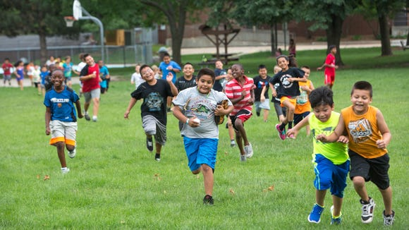 Kids run as they warm up on Monday, June 23, 2014,