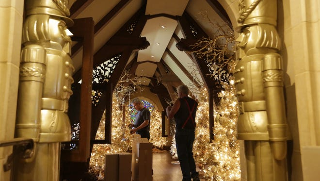 John Ranes of the Frameworks Shop and  Tom Haase place the nutcrackers in their cases as the Paine Art Center and Gardens prepared for the opening of Nutcracker in the Castle Nov. 16.