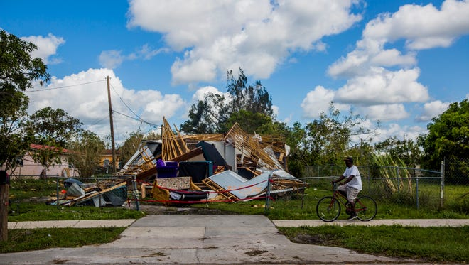 A man rides his bike by a trailer that was destroyed by Hurricane Irma in Immokalee on Tuesday, Sept. 12, 2017.