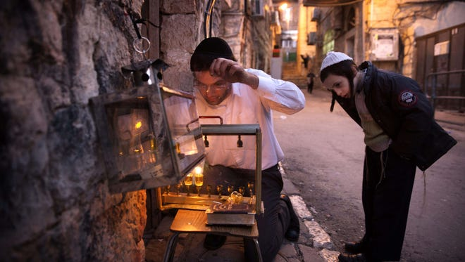 An Ultra-orthodox Jewish man lights candles on the second night of the Jewish holiday of Hanukkah, in a religious neighborhood of Jerusalem, on Dec. 7, 2015.