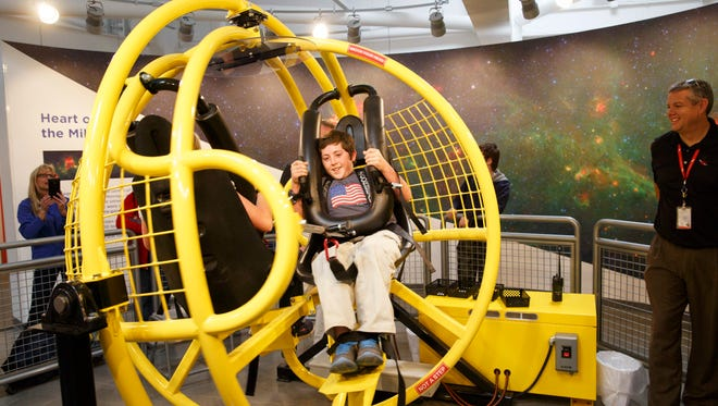 A young visitor takes a turn on the G-Shock simulator, which subjects the would-be astronaut to rapid acceleration comparable to what an actual astronaut might feel in flight.