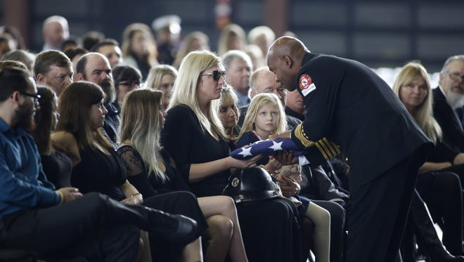 TFD Engineer Jeffrey Atkinson's widow, Nina Atkinson, is presented with the flag that covered his casket at his funeral held Monday at the Center of Tallahassee.