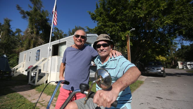 Sam Powers sits on his tricycle next to repairman Steve Nicks in front of Powers' home in Covered Wagon Mobile Home Park.