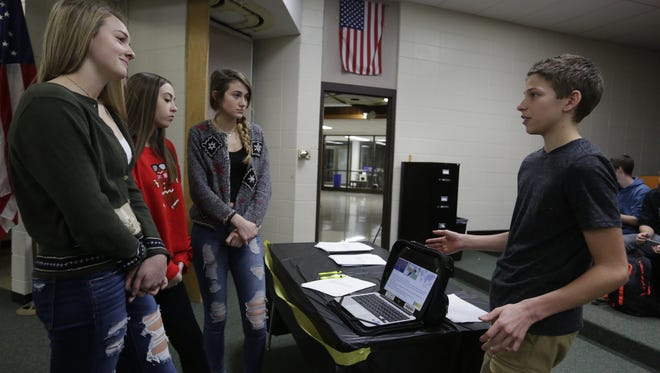 Oshkosh North Communities student Matthew Noe talks to Ashley Gorst, Madison Hurst, and Autumn Kephart about Turkey's Istanbul 10 and how they are imprisoned. The Communities at Oshkosh North program held a letter-writing event during the school day on Tuesday. The ninth- and 10th-graders will be educating high school students and community members on human rights cases.