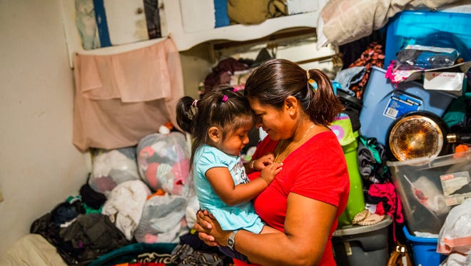 Eustolia Flores takes a break from folding clothes and shares a moment with her daughter Jocelyn, 1, in Immokalee on Thursday, Oct. 5, 2017. Flores' trailer was destroyed in Hurricane Irma.