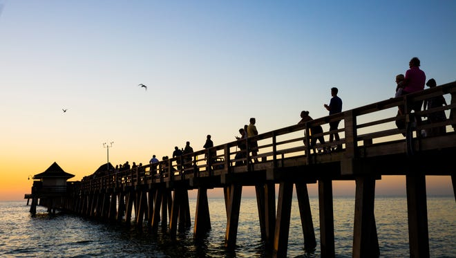 People watch the sunset at the Naples pier on Wednesday, Dec. 6, 2017. The Naples City Council is deciding whether to allow the sale of beer and wine at the well-known landmark.