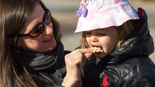Brynn Tannenbaum, 2, of Las Cruces and her mother Ilana try campfire Christmas cookies made at the New Mexico Farm & Ranch Heritage Museum on Saturday, December 23, 2017. The two-year-old helped to make the cookies that she was able to eat later.