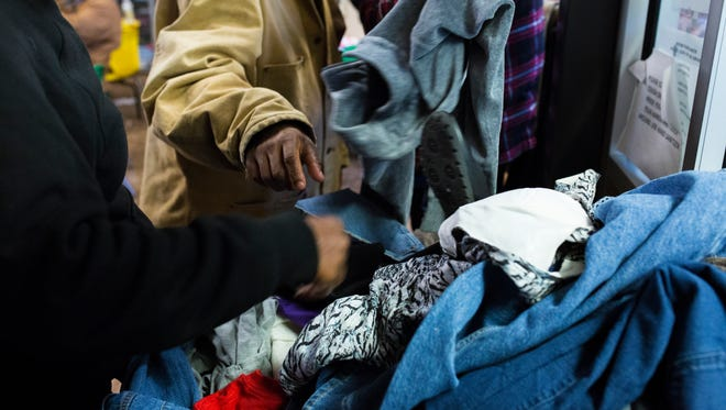Homeless Corpus Christi residents pick through donated jackets at Mother Teresa Shelter Tuesday Jan. 2, 2018. Many people come to the shelter to get out the cold weather.