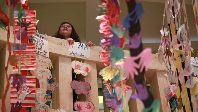 Anahi Ramirez hangs children's artwork in the Capitol Rotunda last year  for the start of Children's Week, which aims to provide a platform for children's advocates to reach the legislators.
