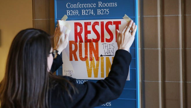 In this Dec. 9, 2017, photo, Lianna Stroster posts a sign directing to a women's candidate training workshop at El Centro College in Dallas.
