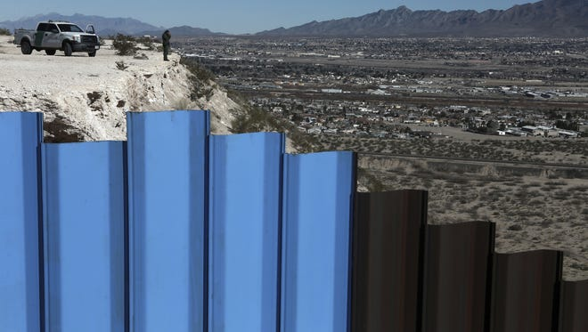 A Border Patrol agent watches over the fence separating Anapra, Mexico, and Sunland Park, N.M.