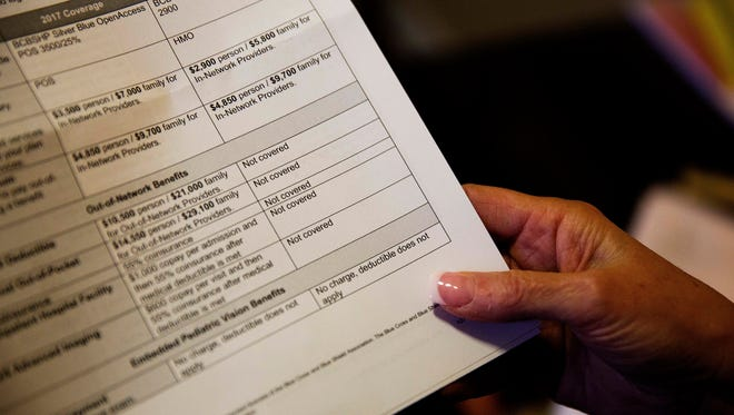 Gail Trauco, owner of The PharmaKon, looks over her health insurance benefit comparison chart which shows out-of-network coverages dropped for 2018, at her home office in Peachtree City, Ga. Most companies' health care plans are set for 2018, but there will be some changes when it comes time to choose policies that begin later in the year or in 2019