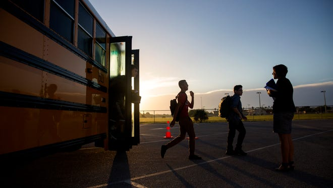Freshman students get off the bus for their first day of school at the temporary campus for Bonita Springs High School while the new school building is built on Thursday, August 10, 2017. A class of about 240 students will work out of the 15 portable classrooms located near Estero High School this year.