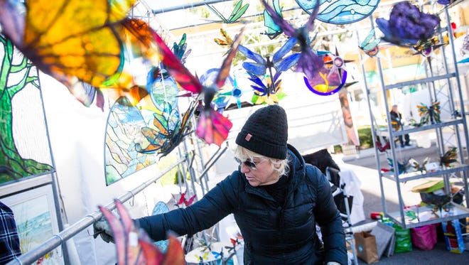 Debi Dwyer places stained glass pieces in her display at the 22nd annual Naples New Year's Art Show on Saturday, Jan. 6, 2018, on Fifth Avenue South.