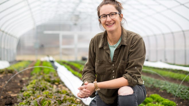 In this Monday, Dec. 11, 2017 photo, Jenny Quiner, owner of Dogpatch Urban Gardens poses in her greenhouse in Des Moines, Iowa. Dogpatch Urban Gardens is the only for-profit farm in Des Moines city limits — the realization of one of Quiner's dreams.