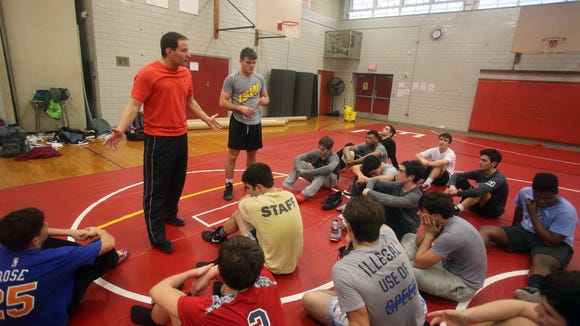 Anthony Rodrigues, coach of the Fox Lane High School wrestling team, and his son Steven, talk to the team after practice  Jan. 27, 2018. Steven, who wrestled at Fox Lane, went on to become an All-American college wrestler. After coaching wrestling last year in Stamford, CA., he returned home and is assisting his father in coaching the Fox Lane team.