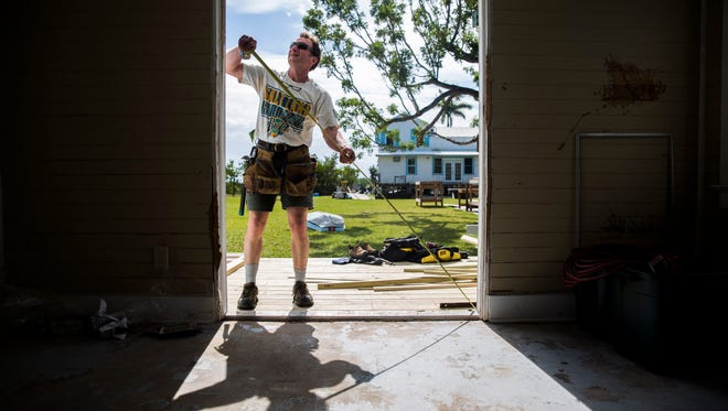 Buzz Kuhns, 59, measures the doorway of a building to replace it's doors at the North Carolina Outward Bound School in Everglades City on Thursday, Jan. 25, 2018.