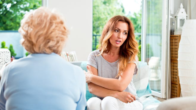 Mid adult woman talking with her mother at home.