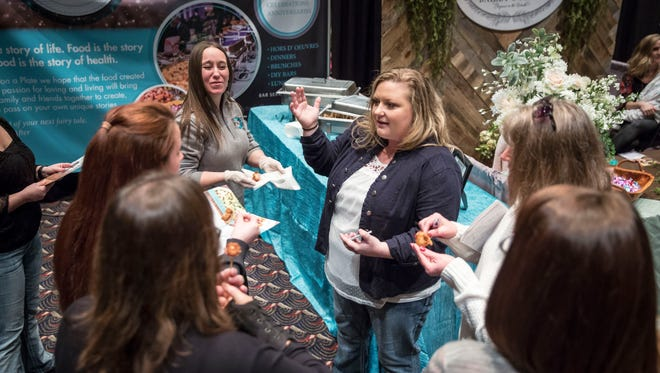 Victoria Brewer, owner of Once Upon A Plate, talks with potential clients at the East Central Indiana Wedding Expo at the Horizon Convention Center.