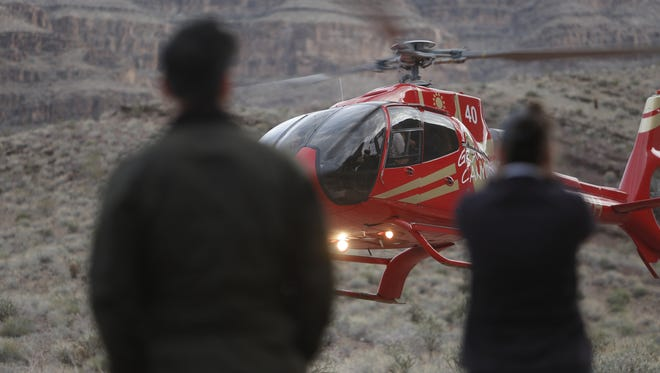 A helicopter flies near the scene of a deadly helicopter crash in the Grand Canyon on Feb. 10, 2018.