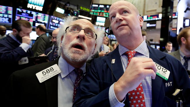 Traders Peter Tuchman, left, and Patrick Casey work on the floor of the New York Stock Exchange on Feb. 8.