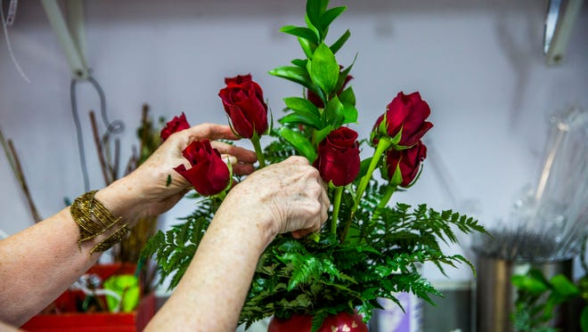 Florists work in the back of Petals & Presents Florist in Estero on Monday, Feb. 13, 2018.