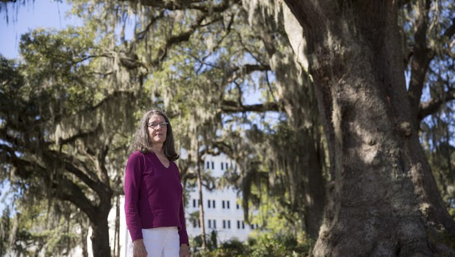 Ann Bidlingmaier, pictured Jan 23, poses under a massive live oak on the list for removal according to the conceptual plan for the Cascades Project.