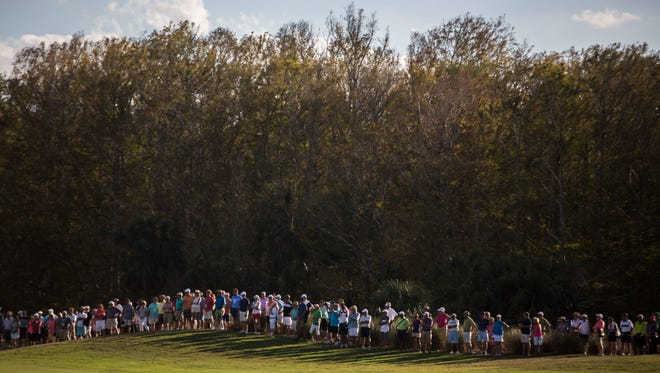 Spectators line up along the pathway as they watch the final ground of golfers make their way to the 18th hole during the final day of the Chubb Classic in Naples this year.