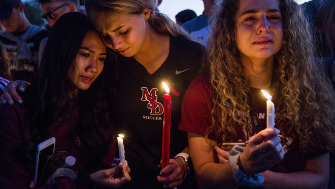 USA TODAY NETWORK Feb. 15, 2018; Parkland, FL, USA; From left, juniors Sidney Ho, Jordan Strauss, and Kendall Edgren mourn together during a candlelight vigil at Pine Trails Park after a shooting at Marjory Stoneman Douglas High School on Wednesday that took 17 lives.