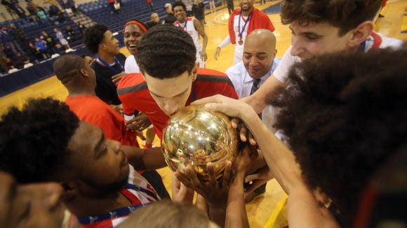 Alexander Hamilton celebrates with the Gold Ball trophy after capturing the Section 1 Class C boys championship with a 66-47 win over Haldane at Pace University in Pleasantville Feb. 24, 2018.