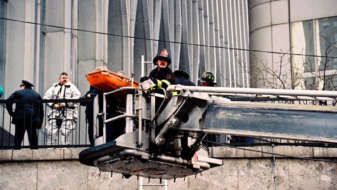 In this Feb. 26, 1993 file photo, firefighters remove a victim on a gurney outside one of the World Trade Center's twin towers in New York, after a car bomb in an underground garage rocked the complex.