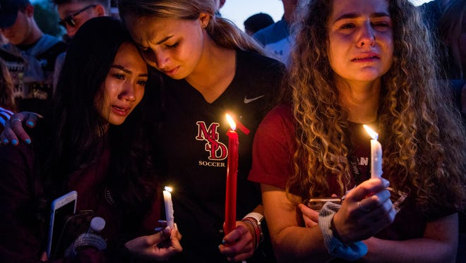 From left, juniors Sidney Ho, Jordan Strauss, and Kendall Edgren mourn together during a candlelight vigil at Pine Trails Park in Parkland, Fla. on Thursday, Feb. 15, 2018 after a shooting at Marjory Stoneman Douglas High School in Parkland, Fla. on Wednesday that took 17 lives.