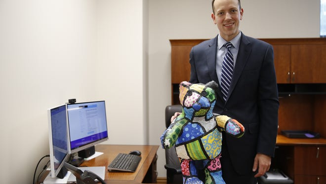 Capital Regional Medical Center's new CEO Alan Keesee poses at his desk Tuesday with a paper-mache bear from his last job as COO of Sunrise Hospital and Medical Center & Sunrise Children's Hospital in Las Vegas, Nevada. While the rest of his office decorations haven't arrived yet, Keesee says his colleagues from the children's hospital mailed him the bear because they know how much he loved it.