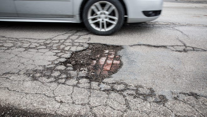 A large pothole on West Jackson Street shows the brick work underneath the street, and is one of hundreds across the area. Repair efforts have been hindered as crews are forced to use cold patch until asphalt plants begin to make hot patch.
