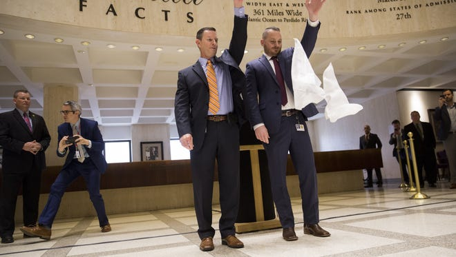 House Sergeant at Arms Russell Hosford, left, and Senate Sergeant at Arms Tim Hay drop their hankies  at 4:17 p.m. Sunday in the Capitol rotunda during the annual sine die ritual that marks the end of the 2018 legislative session.