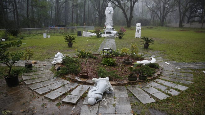 Vandalized statues at Vien Giac Buddhist Monastery on North Monroe Street, pictured Monday.