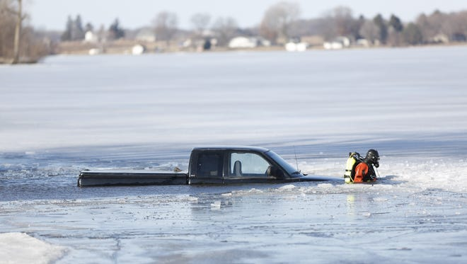 A member of the Fond du Lac County Dive Team walks alongside a truck which went in to Fox Lake Monday morning.