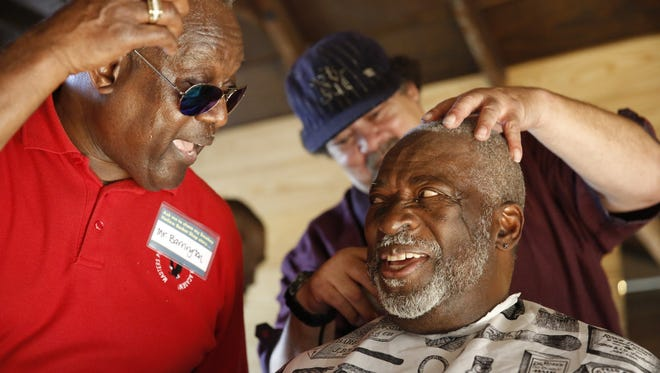 Michael Barrington, left, jokes with Delmas Barber as he gets a haircut from Melvin Gilliam during the grand opening of the Smokey Hollow Barber Shop at the Smokey Hollow Commemoration in Cascades Park Monday.