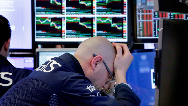 Specialist Mario Picone works at his post on the floor of the New York Stock Exchange on Friday.