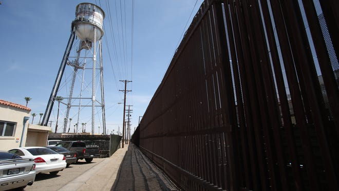 Vehicles are seen parked at the border wall in downtown Calexico on April 10, 2018.