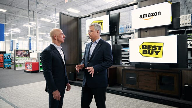 Amazon CEO Jeff Bezos (left) and Best Buy CEO Hubert Joly (right) tour a Best Buy store in Bellevue, Wash. on April 17, 2018.
