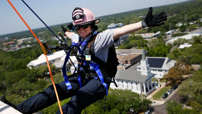 Firefighter Sarah Cooksey rappels down the DoubleTree hotel as part of an annual Over the Edge fundraiser benefitting public safety initiatives.