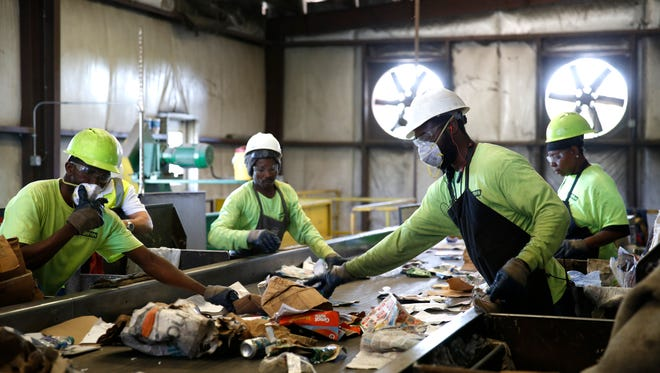 Contamination, any items that should never have made their way into the recycling stream, is removed by hand as the recycled material is sorted at the Marpan recycling facility Thursday.