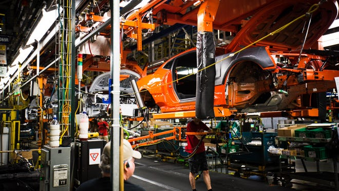 The frame of a Camaro Hot Wheels Edition is carried along the assembly line.