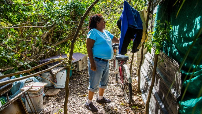 "In this file photo from March 2018, Jesusita ""Susanna"" Rodriquez hangs wet clothes in her camp in Immokalee. Rodriquez was left homeless after Hurricane Irma hit Southwest Florida six months ago."