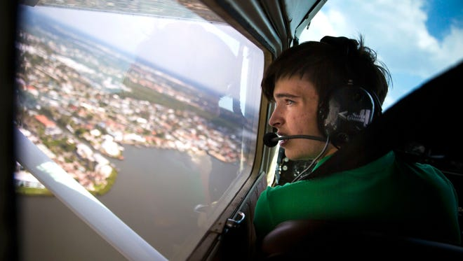"Sailor Robinson looks over the left wing of the 1960 Cessna 172 as he performs a ""touch and go"" during his last flying lesson before his first solo flight on Tuesday, May 1, 2018, at the Naples Municipal Airport. Sailor soloed on his 16th birthday, on Wednesday, May 2, 2018, the youngest age a pilot is able to make a first solo flight."