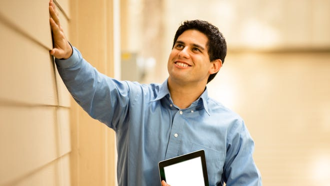 Latin descent building inspector, exthe home inspection can seem a little dauntingterminator, architect, building contractor, engineer, or insurance adjuster examines a building/home's exterior siding wall and window.  He holds a digital tablet.