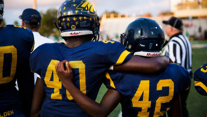 Defensive back Nesley Laguerre and linebacker Jean Baptiste stand together on the sidelines during Naples High's spring game in May.